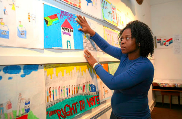 """A teacher hangs up pictures her students have made that say """"freedom to vote"""""""