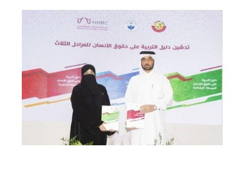Two people show the new guide on human rights education developed in Qatar
