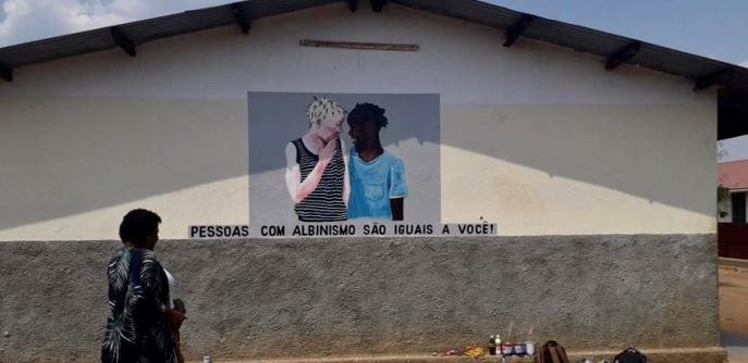 """A painting on a wall depicting a white and a black boy with the caption, """"People with albinism are the same as you"""""""