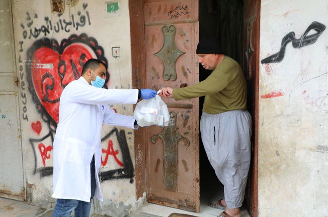 A doctor hands some groceries to a man outside of his house