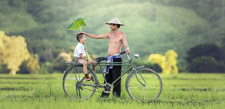 A man gives his son a ride on his bicycle.