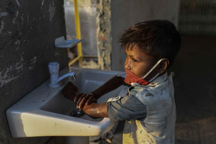 A little boy washes his dirty hands in the sink