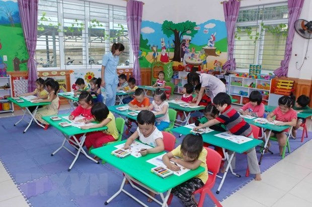 A classroom of children learns by coloring while teachers walk around helping them