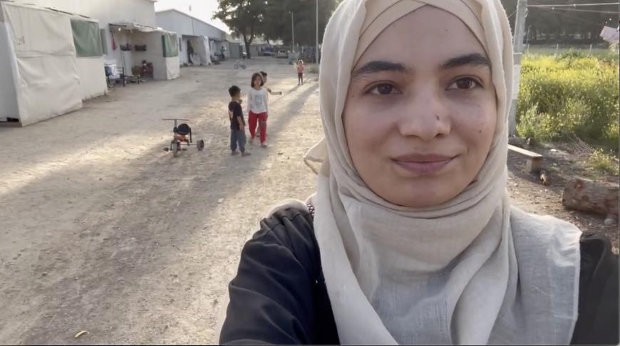 A girl takes a selfie of herself and some children in the refugee camp