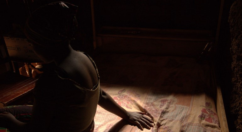 child sitting on a bed in a dark room